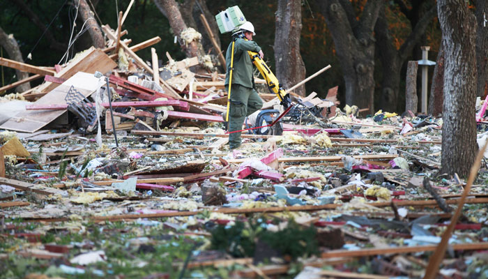 Wednesday morning, a ranger from the Department of Public Safety navigates through the debris after an explosion destroyed a two-story home in Victoria, Texas. Officials are investigating to find the cause of the blast Wednesday that killed 26-year-old Haley Singer, Victoria County Sheriff T. Michael O'Connor said. Firefighters found her 4-month-old daughter, Parker, alive in the debris. The child was being treated at a hospital in San Antonio, about 100 miles to the northwest. (AP Photo/The Victoria Advocate, Kathleen Duncan)