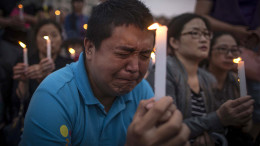 A man reacts during a candle light vigil by locals and family members of passengers onboard the capsized cruise ship in Jianli county  in southern China's Hubei province Thursday.  Rescuers cut three holes into the overturned hull of a river cruise ship in unsuccessful attempts to find more survivors Thursday.  (Chinatopix Via AP)
