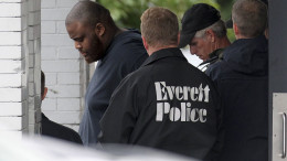 In this Tuesday, June 2, 2015 photo, authorities remove David Wright from a house in Everett, Mass., after a day-long police investigation at the property. Wright, a relative of Usaama Rahim, was ordered held Wednesday on a charge of conspiracy with intent to obstruct a federal investigation in the Rahim case. Rahim, who was under surveillance by terrorism investigators, was shot and killed after he wielded a knife at a Boston police officer and an FBI agent. (Boston Herald/John Wilcox via AP)