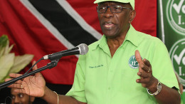 Former FIFA vice president Jack Warner speaks Wednesday at a political rally in Marabella, Trinidad and Tobago. One moment, Jack Warner is on TV telling his countrymen in Trinidad that he fears for his life. An hour later, he's standing on a packed narrow street at a political rally telling supporters that he fears nothing. Indicted by the United States on charges of racketeering, wire fraud and money-laundering, Warner is officially an internationally wanted man, listed as one of Interpol's most wanted persons. (AP Photo/Anthony Harris)