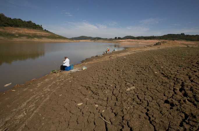 Fisherman sit on cracked land at Sao Paulo dam