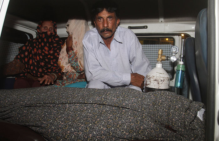 Mohammad Iqbal, right, sits in an ambulance next to the body of his pregnant wife, Farzana Parveen, who was stoned to death by her own family in Lahore, Pakistan on Tuesday. Nearly 20 members of Parveen's family attacked her and Iqbal with batons and bricks, according to police. (K.M. Chaudary/The Associated Press).
