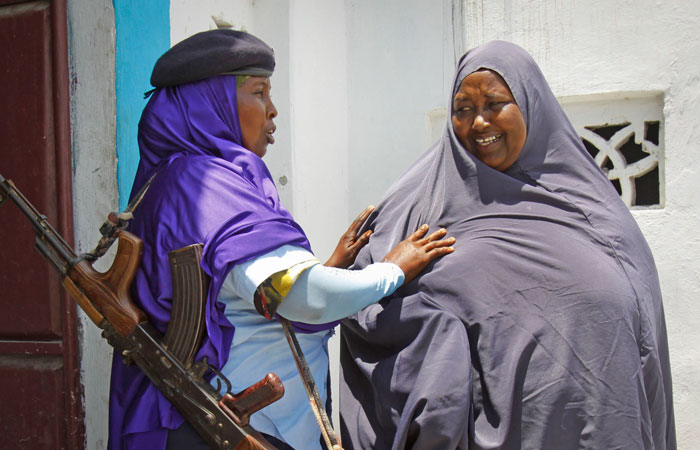 A female Somali soldier, left, searches a civilian before she enters a police station in Mogadishu, the nation's capital, on Sunday, March 30, 2014. There are at least 1,500 women serving in the Somali army, though most are not allowed to fight on the front lines.