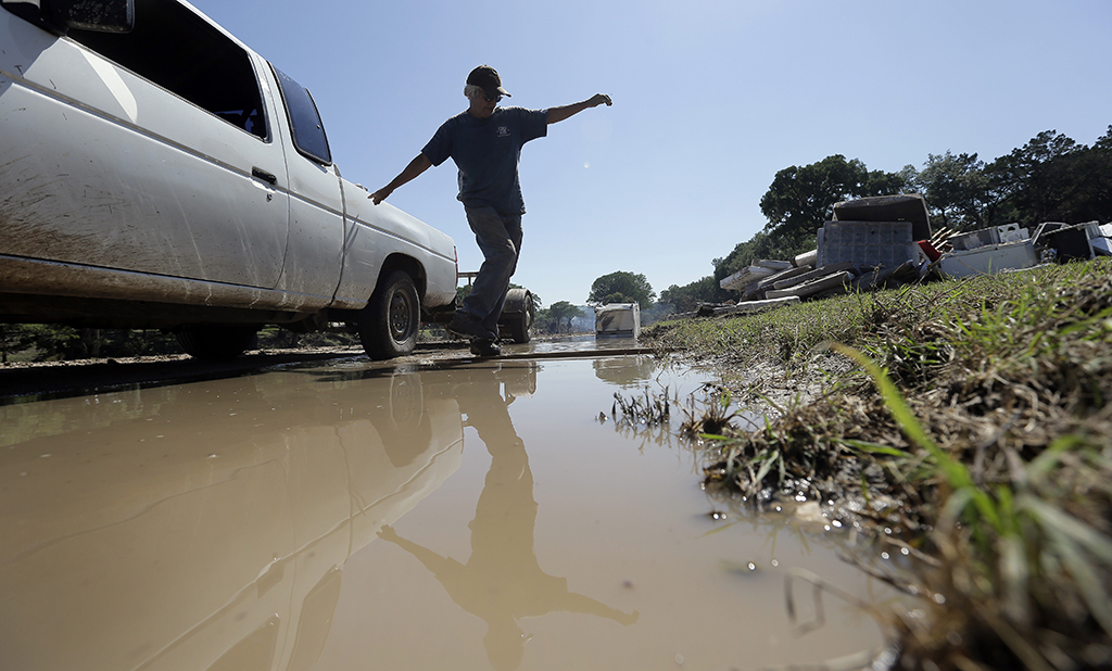 Johnny  Rodriguez uses a plank to cross standing water as he works along the Blanco River, Friday, May 29, 2015, in Wimberley, Texas. Search efforts continue for those persons who went missing from the Memorial Day weekend floods in Central Texas. (AP Photo/Eric Gay)