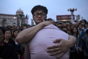 Relatives of passengers onboard the capsized cruise ship comfort each other during a candle light vigil in Jianli county  in southern China's Hubei province, Thursday.  Rescuers cut three holes into the overturned hull of a river cruise ship in unsuccessful attempts to find more survivors Thursday.  (Chinatopix via AP)
