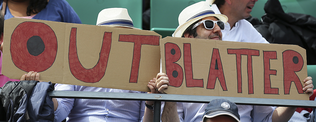 "Two spectators hold signs reading ""Out Blatter"", referring to newly re-elected FIFA president Sepp Blatter during the quarterfinal match of the French Open tennis tournament between Spain's Garbine Muguruza and Lucie Safarova of the Czech Republic at the Roland Garros stadium, in Paris, France, Tuesday, June 2, 2015. Blatter said Tuesday he will resign from his position amid corruption scandal. (AP Photo/David Vincent)"