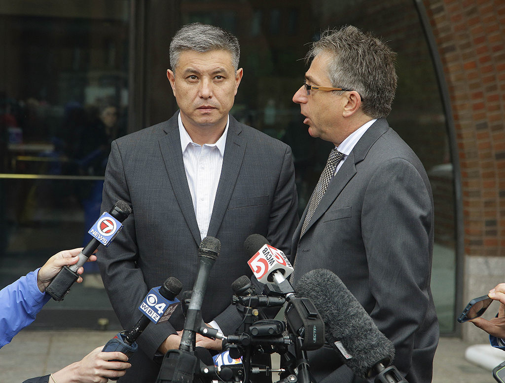 Murat Kadyrbayev, left, the father of Dias Kadyrbayev, 21, stands outside Federal court with his interpreter, Alexander Tetradze, Tuesday, June 2, 2015, answering reporter's questions about the sentencing of his son, a college friend of Boston Marathon bomber Dzhokhar Tsarnaev, sentenced Tuesday to six years in prison after he apologized to the victims and their families for not calling police when he recognized photos of Tsarnaev as a suspect Tuesday, June 2, 2015, in Boston. Kadyrbayev, 21, pleaded guilty last year to obstruction of justice and conspiracy charges for removing items from Tsarnaev's dorm room after recognizing his friend in photos released by the FBI. (AP Photo/Stephan Savoia)