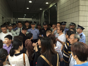 Relatives of Shanghai passengers on board a cruise ship that capsized in central China, attempt to storm a government office to demand for action after the tourist agency which organized the tour failed to help them, in Shanghai, China, Tuesday, June 2, 2015. Such quick outrage mirrors the responses of victims' relatives from other recent disasters such as last year's disappearance of Malaysian Airlines Flight 370, which carried hundreds of Chinese travelers when it vanished from radars. (AP Photo)