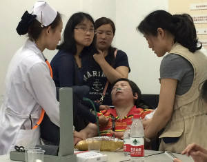 A relative of Shanghai passengers on board a cruise ship that capsized in central China, is attended to by a medical worker as she waits for answers at a government office in Shanghai, China, Tuesday, June 2, 2015. Relatives storm a government office to demand for action after the tourist agency which organized the tour failed to help them. (AP Photo)