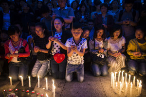 Locals and relatives of passengers onboard the capsized cruise ship pray during a candle light vigil in Jianli county, in southern China's Hubei province, Thursday. Rescuers cut three holes into the overturned hull of a river cruise ship in unsuccessful attempts to find more survivors Thursday.  (Chinatopix Via AP)