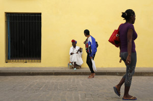 In this Dec. 19, 2014 file photo - A street entertainer waits for tourists in Old Havana, Cuba. The thawing of U.S.-Cuba relations has inspired many Cubans to think big. Visits by Americans were up 36 percent between January and early May of 2015 compared to the same period a year ago, and up 14 percent among all international arrivals. That surge is likely to continue as interest in the destination grows and it gets easier for Americans to travel there. (AP Photo/Desmond Boylan, File)